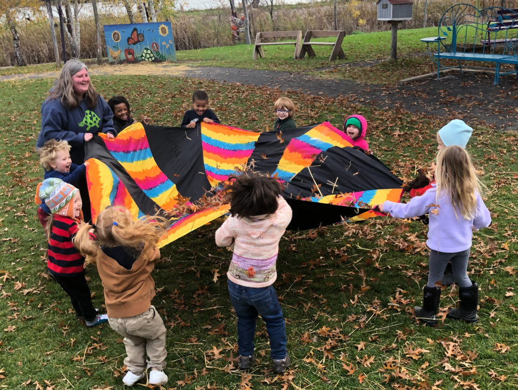A white teacher and several small children of different races lift a colorful parachute blanket with fallen leaves in the center together. All of them are smiling.