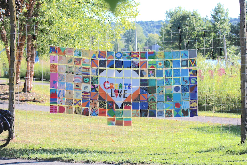 "Colored tile mosaic, in the center, surrounded by a white heart as the words ""Create Love"". Installation at Ithaca Children's Garden in Ithaca, New York."