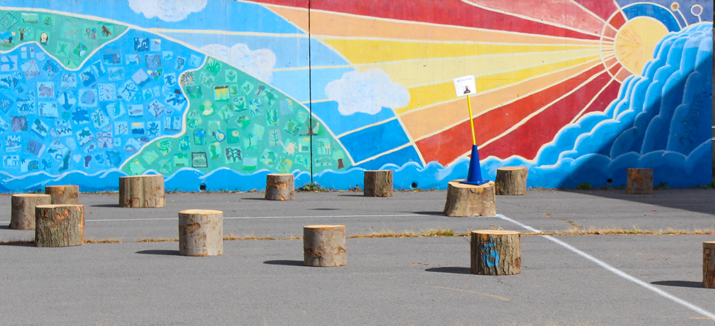 Vibrantly colored mural of a sun and its rays shining on the Earth. Tree stumps placed on the lot in front of it.